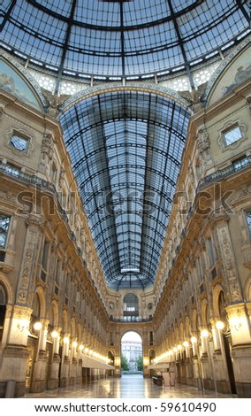 Symmetrical night shot of the hall of the landmark arcade or covered shopping mall, Galleria Vittorio Emanuele II in Milan, Italy, showing the spectacular view of an almost golden gate to luxury - stock photo