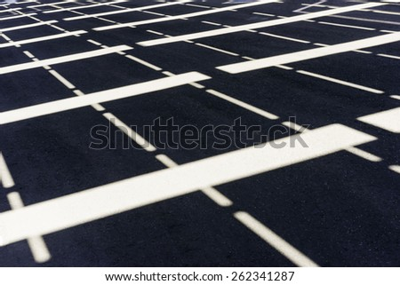 Symmetrical pattern of sunlight and white stripes on asphalt parking lot - stock photo