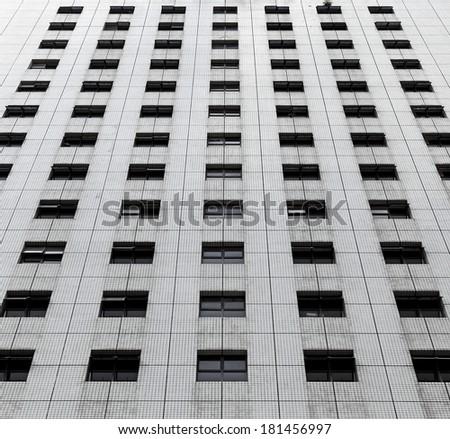 Symmetrical windows on the facade of a concrete skyscraper.  - stock photo