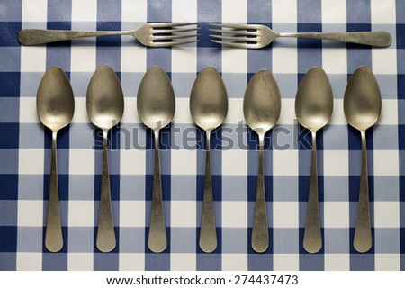 Symmetry of old spoons and forks seen from above and on tablecloth - stock photo