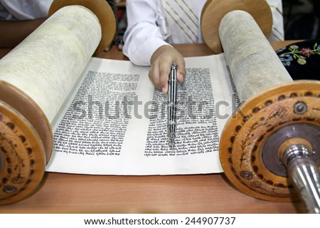 SYNAGOGUE, ISRAEL - MAY 30, 2011: Reading a Torah scroll with the pointer for reading the Torah in the hand - stock photo
