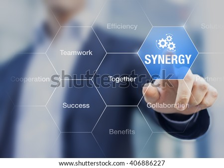 Synergy, concept about obtaining better results from collaboration, conference presentation with businessman in background - stock photo