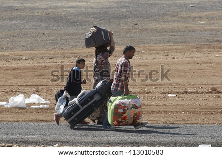 Syrian refugees who escaped from Kobane walking on Turkey-Syria border in Suruc. Sanliurfa, Turkey, 21 May 2014 - stock photo