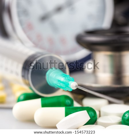 Syringe, different pills, stethoscope and sphygmomanometer useful to illustrate any medical subject - stock photo