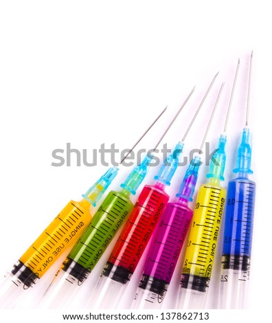 Syringe filled with solution various bright colors - stock photo