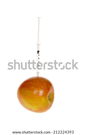 Syringe Needle stuck into an apple as a concept of all the drugs we put into our system through modified foods - stock photo