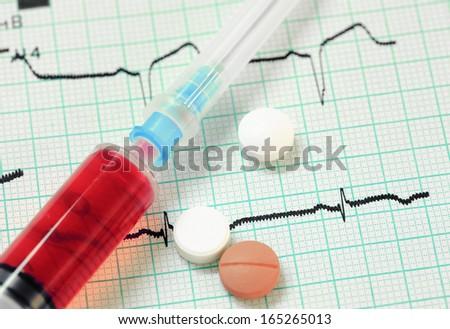 Syringe, pills on an electrocardiogram. Stylish medical background. - stock photo