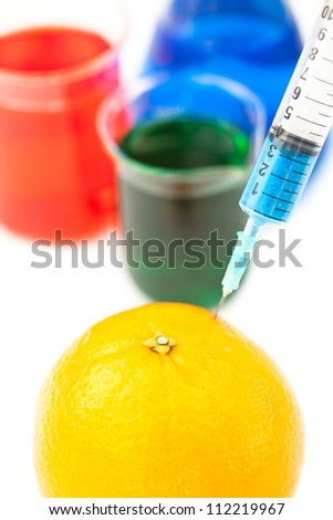 Syringe pricking a lemon against a white background - stock photo