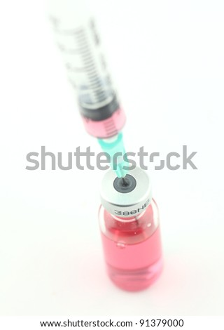syringe sucks the vaccine from a bottle - stock photo