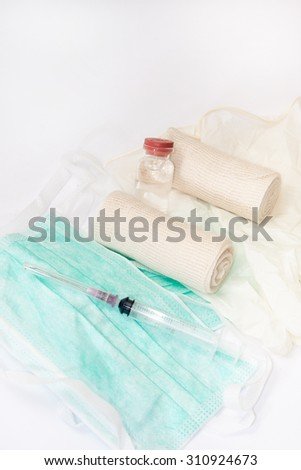 Syringes and bandages on surgical mask and gloves. - stock photo