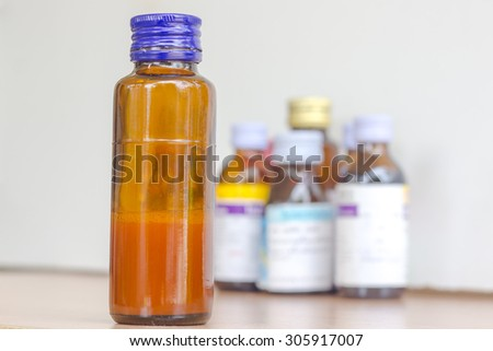 syrup bottle with syrup bottles background - stock photo