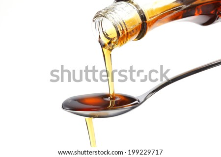 Syrup dripping off a spoon. - stock photo