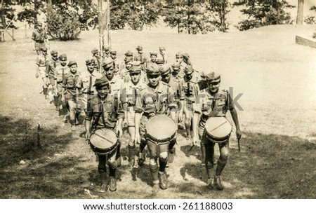 SZCZAWNICA, POLAND, CIRCA 1950's: Vintage photo of group of scouts marching outdoor and playing drums - stock photo