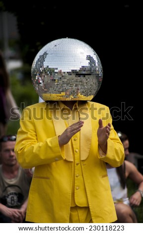 Szczecin, Poland - Mai 23, 2014: Juwenalia, is an annual students' holiday in Poland, usually celebrated for three days in late May. Disco Ball Man in a yellow dress, dancing in the street. - stock photo