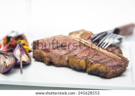 T-bone steak just of the barbecue grill with vegetable spears in the background - stock photo