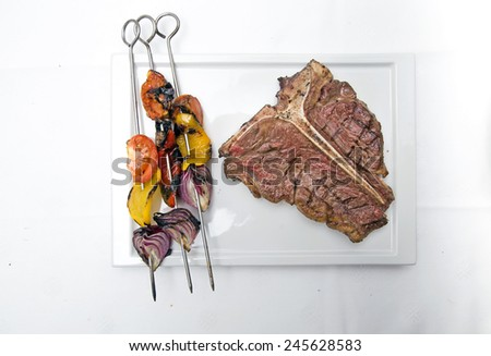 T bone steak on a white plate with grilled vegetable and glass of red wine shot on white - stock photo
