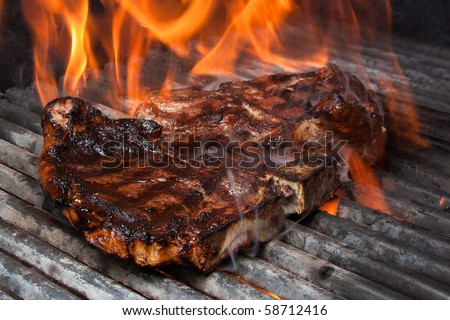 T-Bone Steak on Barbecue Grill Flames - stock photo