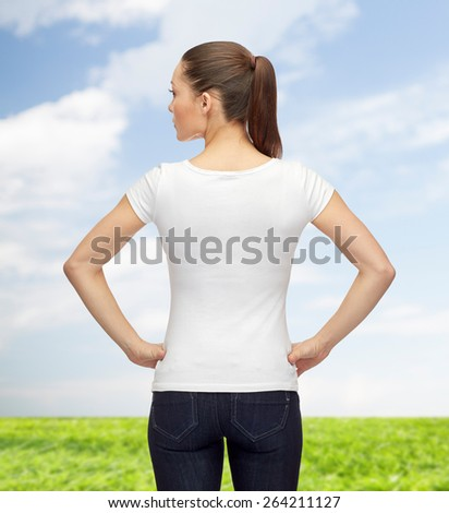 t-shirt design, advertisement and people concept - woman in blank white t-shirt from back over blue sky and grass background - stock photo