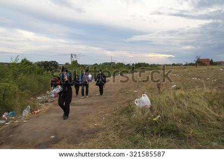 TABANOVCE, MACEDONIA: SEPTEMBER 11, 2015: Immigrants and refugees from Middle East and North Africa crossing Macedonian border. - stock photo