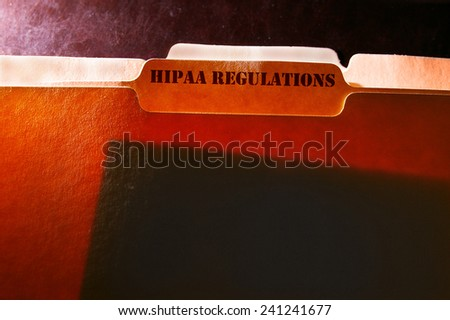 tabbed file folders with HIPAA Regulations text - stock photo