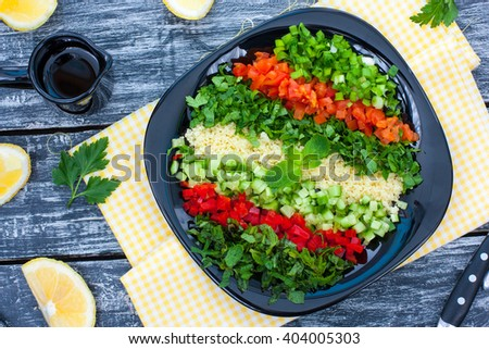 Tabbouleh, couscous salad and fresh vegetables, horizontal, top view - stock photo
