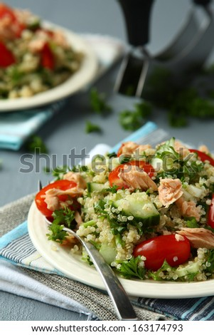 Tabbouleh salad with quinoa, salmon, tomatoes, cucumbers and parsley - stock photo