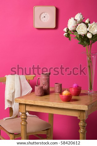 table and a chair in the front of a pink wall - stock photo