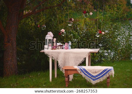 Table and bench in nature with decorations and glass jars with flowers on the tree, picnic, decor, event - stock photo
