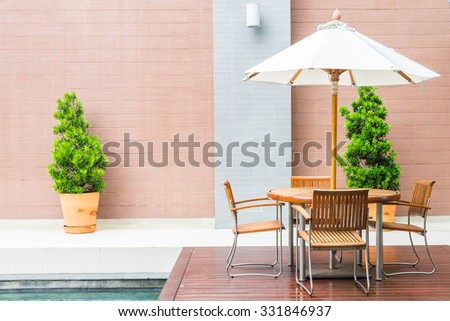 Table and chair with white umbrella outdoor patio - stock photo