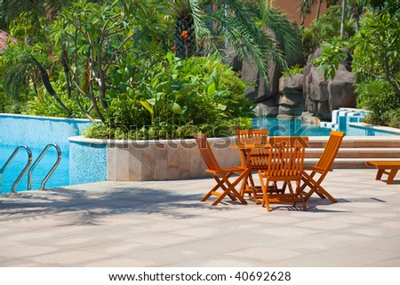 Table and chairs by a swimming pool in the garden - stock photo