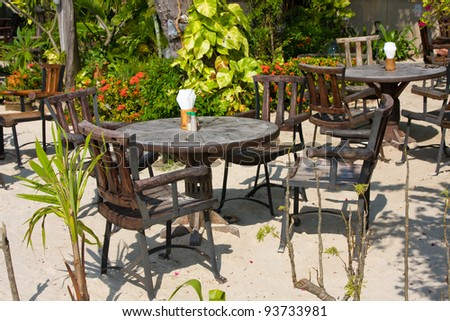 Table and chairs in a tropical garden on the shore, Thailand - stock photo