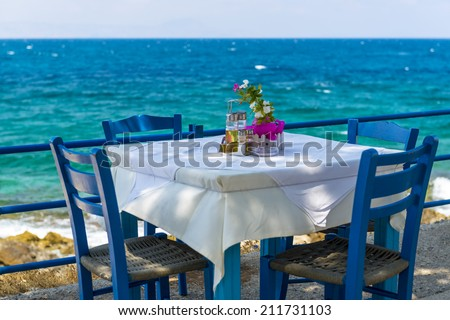 Table And Chairs In A Typical Tavern By The Sea At Rethymnon, Crete, Greece - stock photo