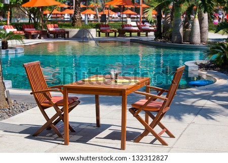 Table and chairs in empty cafe next to the pool, Thailand - stock photo