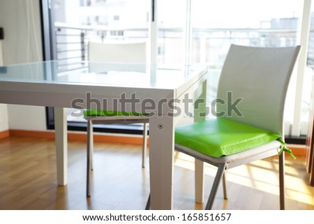 table and chairs in front of windows in the room - stock photo