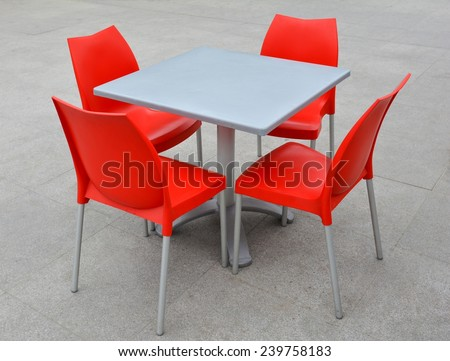 Table and chairs of red color  - stock photo