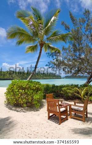 Table and chairs under a palm tree on a tropical beach, Ile des Pins, New Caledonia - stock photo