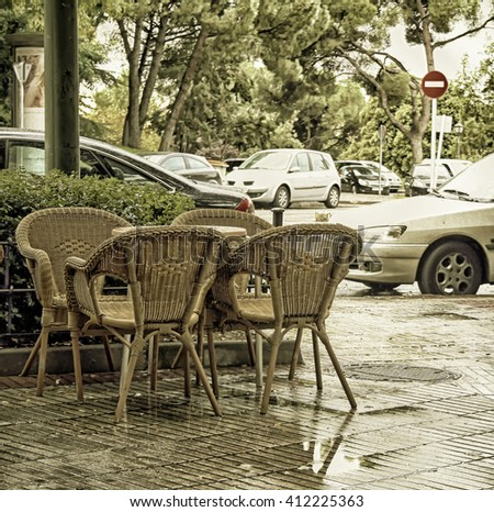 Table and wicker chairs in cafe of Madrid later on rain - stock photo