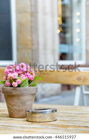 table antique wooden terrace with an ashtray and a pretty plant pink flowers - stock photo