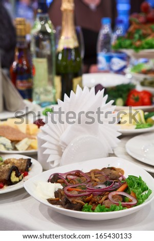 Table appointments with snacks. Plate with marinated mushrooms - stock photo