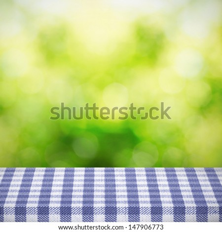 Table blue cloth over natural background - stock photo