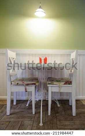 Table for two in cozy cafe with pastel green walls - stock photo
