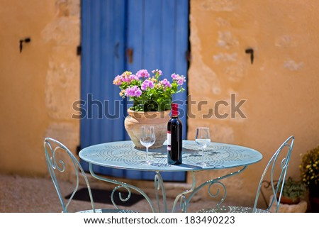 Table for two set with red wine in front of a rustic country house. The wall is painted in ochre  with wooden door in blue. - stock photo