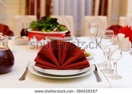 Table in a restaurant with wine glasses, red napkins and cutlery - stock photo