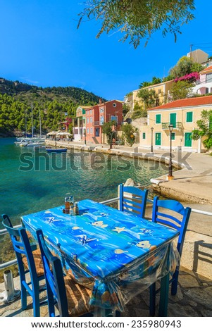 Table in Greek tavern on coast of Kefalonia island in Assos fishing village, Greece - stock photo