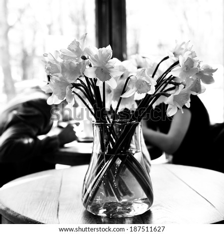 Table in the cafe with lent lily and loving couple at background. Date. Urban lifestyle. Black and white. - stock photo