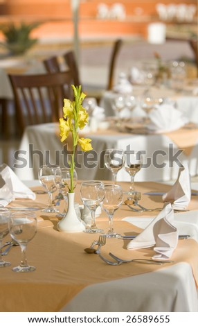 Table in the restaurant with yellow gladiolus - stock photo
