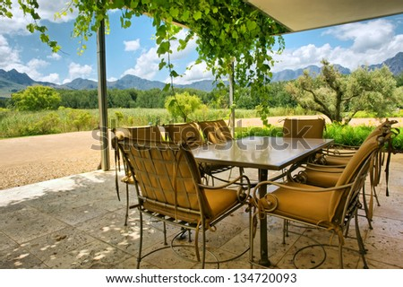 Table in vine-covered pavillion next to magnificent mountains. Shot near Stellenbosch and Cape Town, South Africa. - stock photo