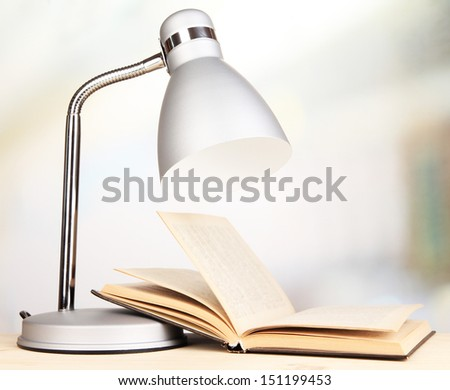 Table lamp and open book in room - stock photo