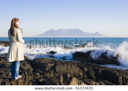 Table Mountain - the world famous landmark in Cape Town, South Africa. Picture taken on a clear Winters day from the Blouberg Strand beach. A girl is standing on some rocks in the foreground. - stock photo