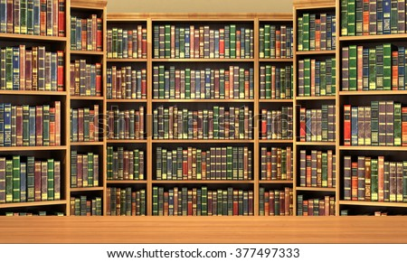 Table on background of bookshelf full of books . Old library. - stock photo